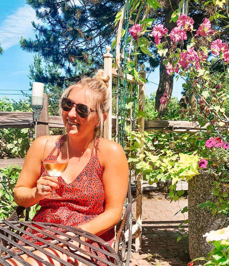 on a patio with greenery and pink flowers drinking a glass of wine
