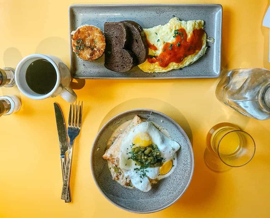 breakfast spread of coffee, eggs, toast, and gravy on a yellow table