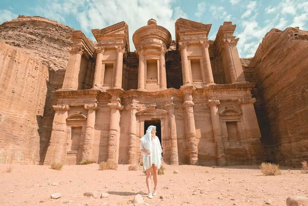 girl in white standing in front of the montastery in petra