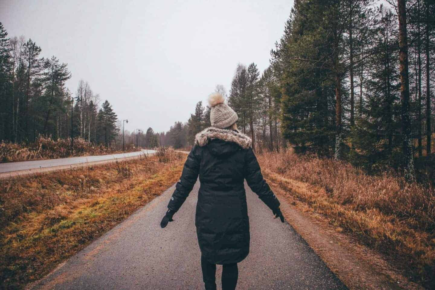 girl walking down grey and dreary lane in finland with big pine trees