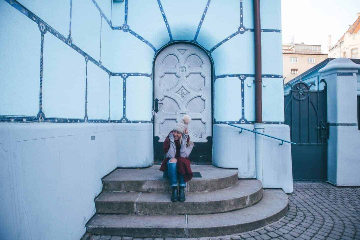 girl sitting in front of blue church