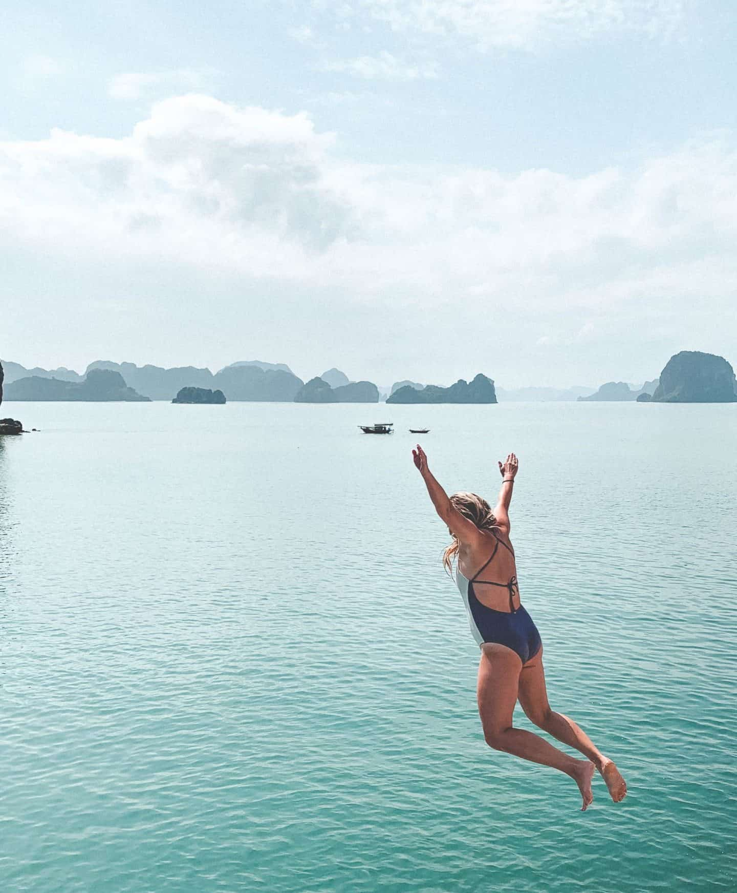 girl jumping from boat into crystal clear water below