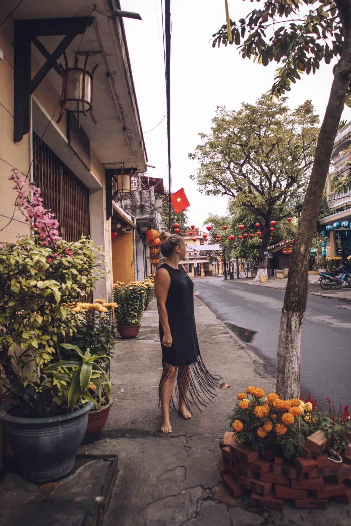 girl in black dress standing in front of vietnam flag