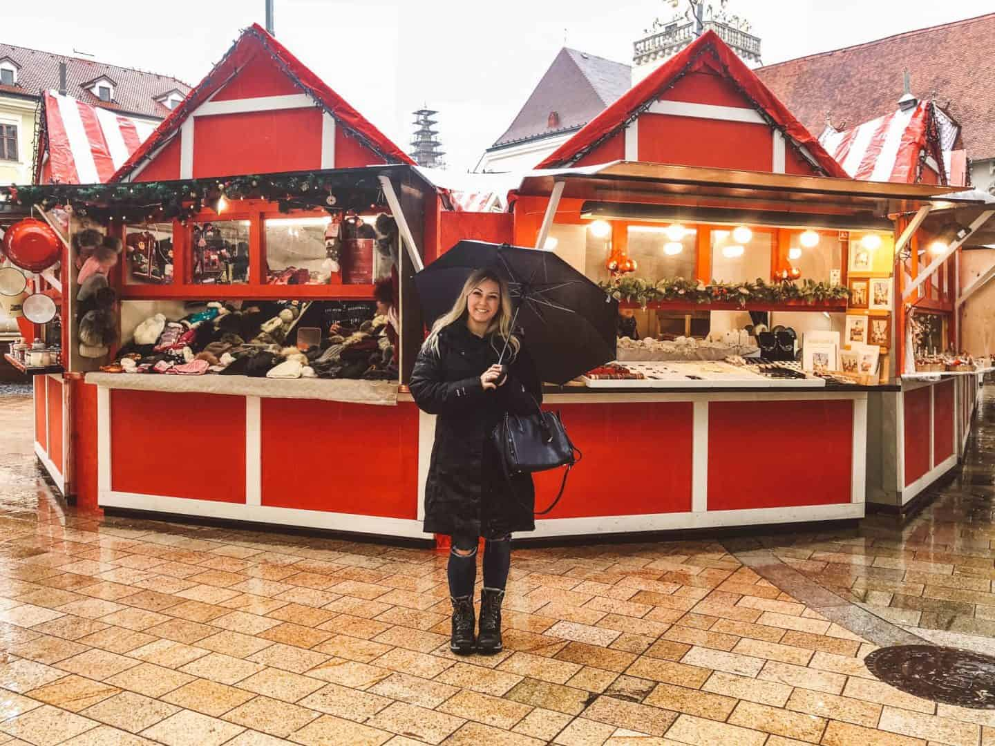 girl with umbrella standing in front of bright red christmas stands