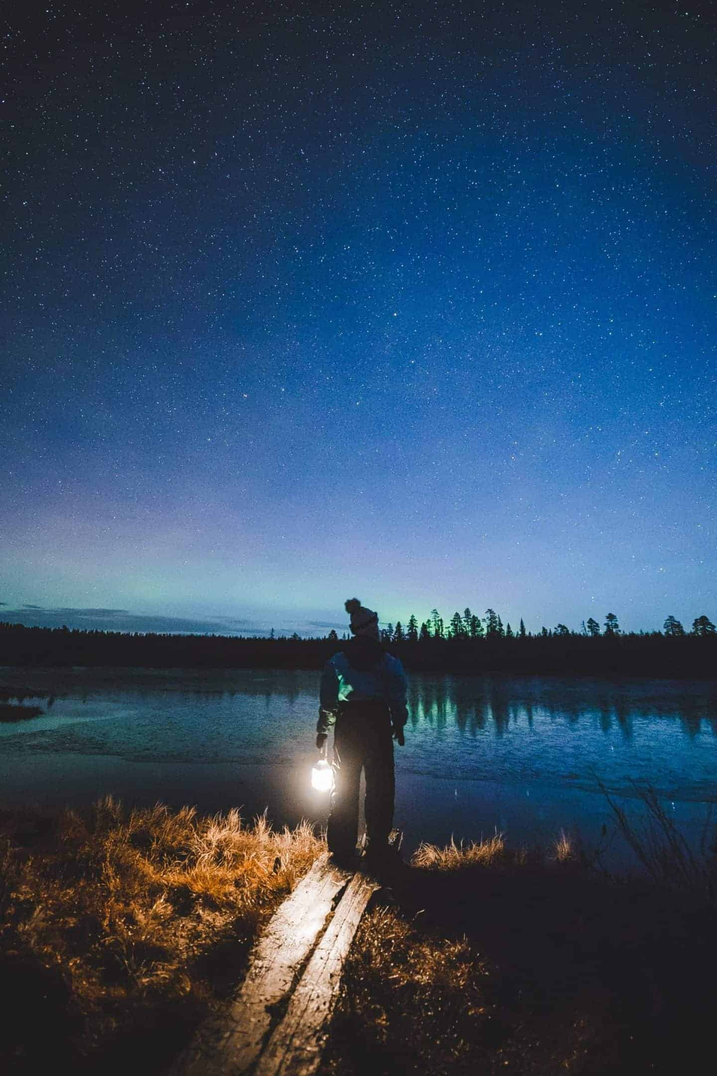 girl with lamp and northern lights in background