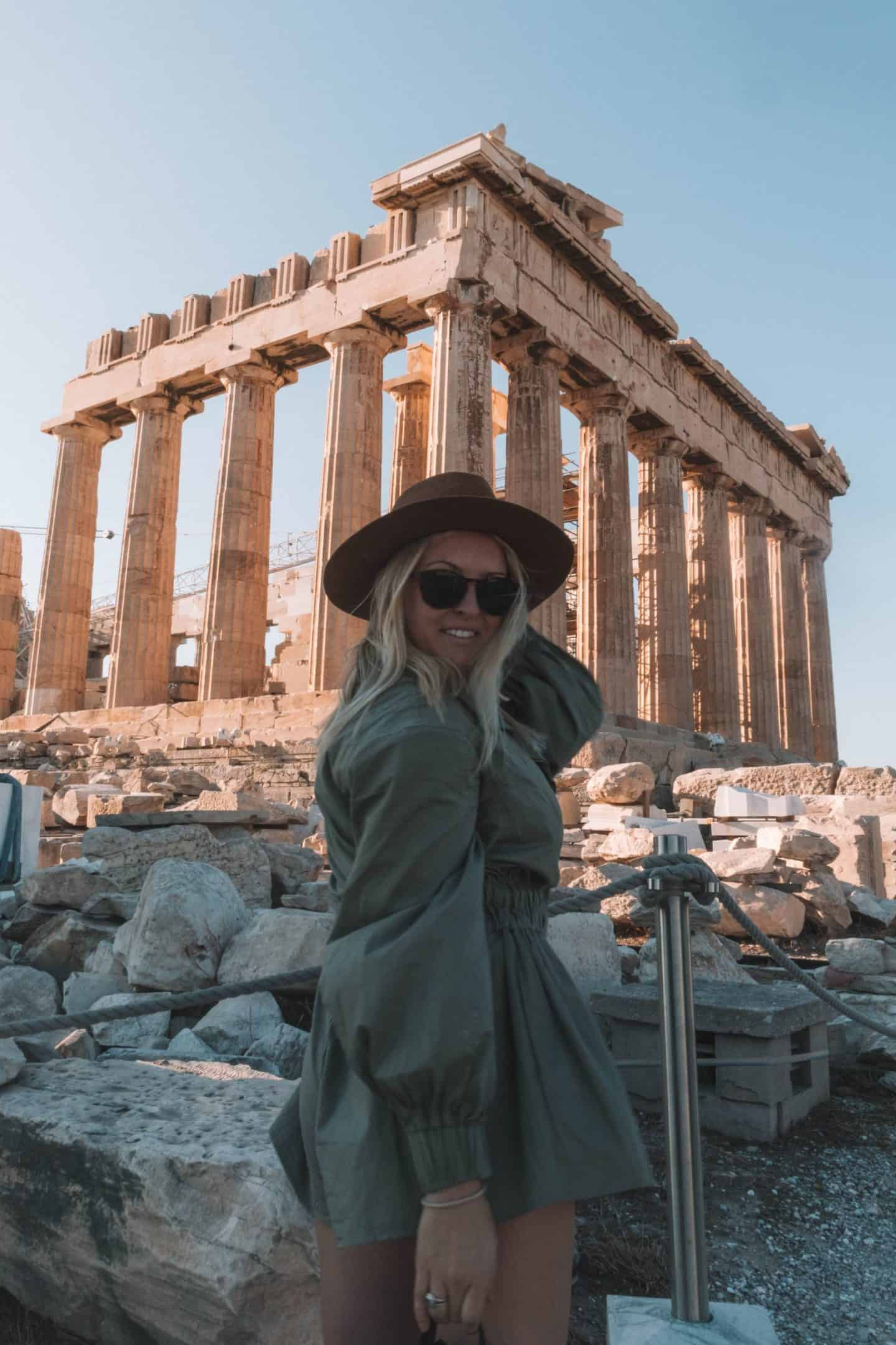 girl smiling in front of the acropolis in athens, greece