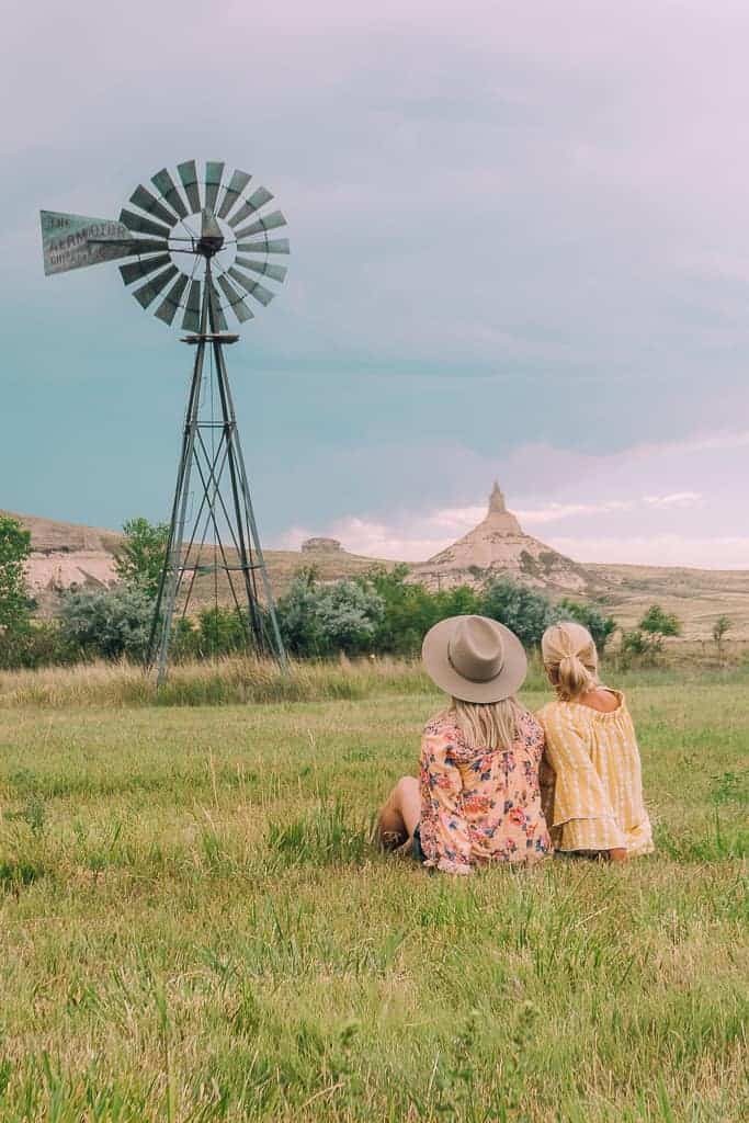 two girls staring out at a grassy field with a windmill in the foreground and chimney rock in the background