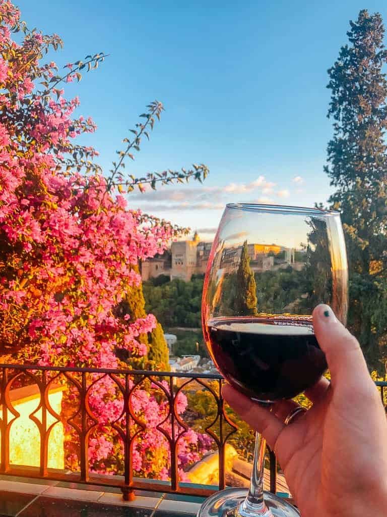 a glass of robust red wine while the sun is setting behind the alhambra