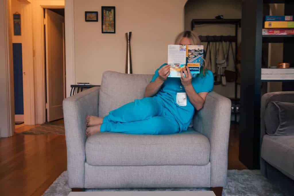 nurse in scrubs reading book about Portugal