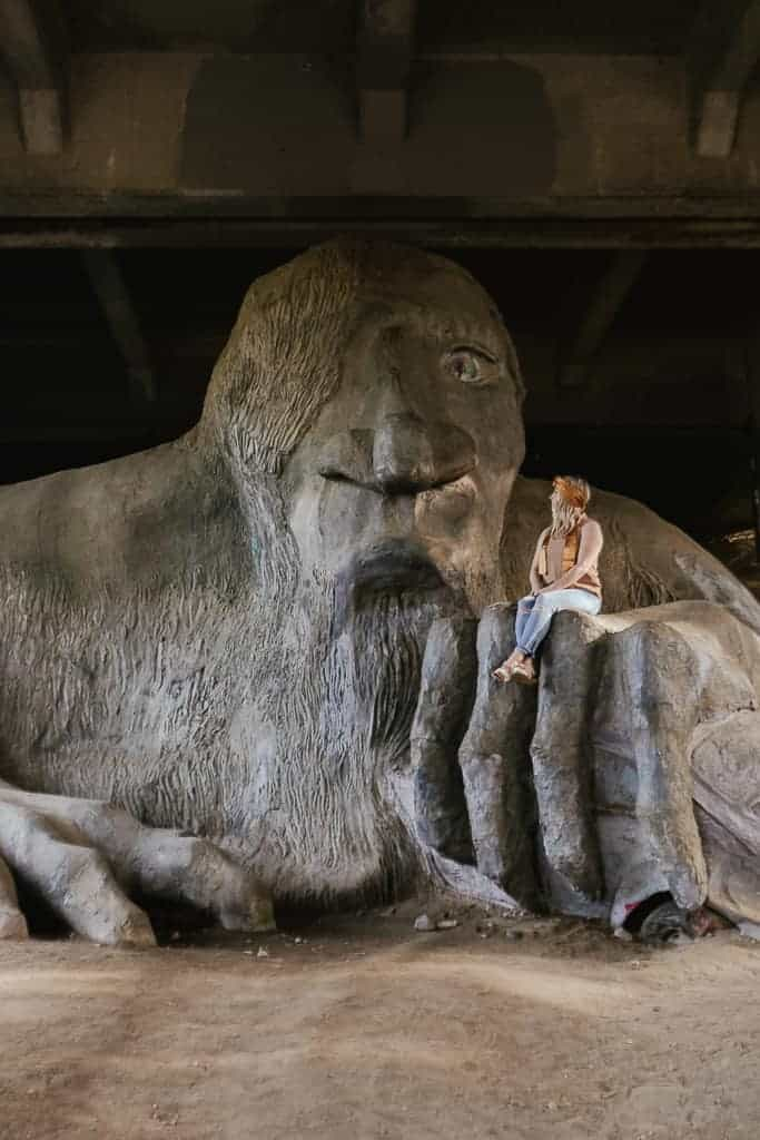 sitting on the hand of the fremont troll sculpture