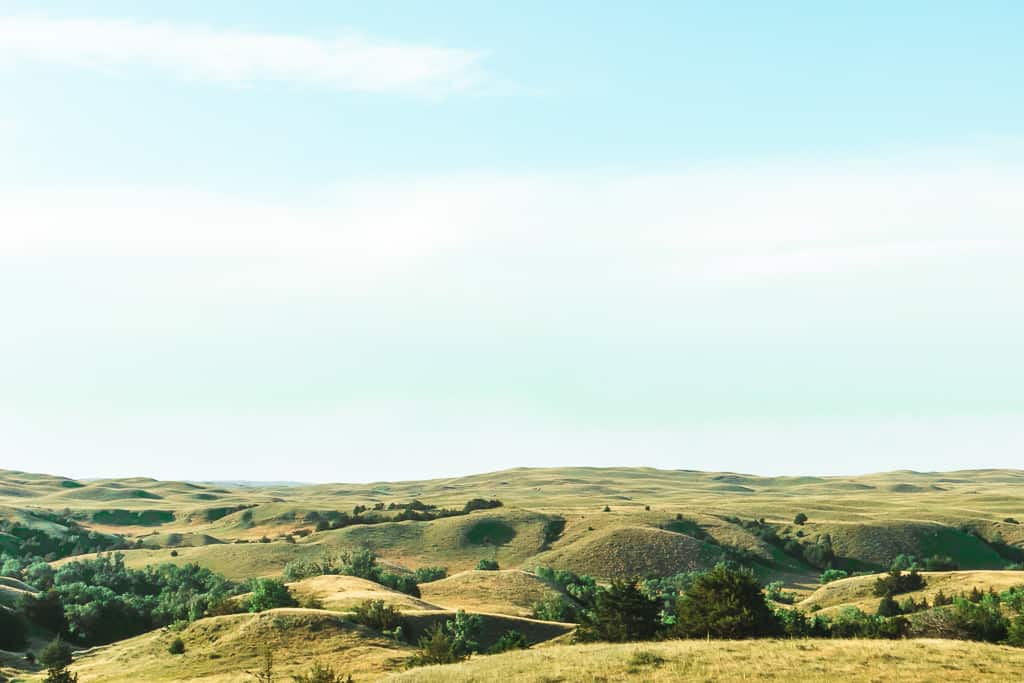the nebraska sandhills - rolling green hills kissing the bright blue sky