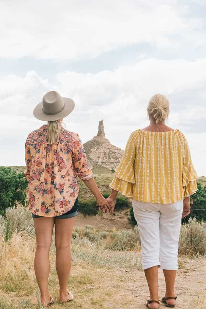 my mom and i holding hands with chimney rock in the background