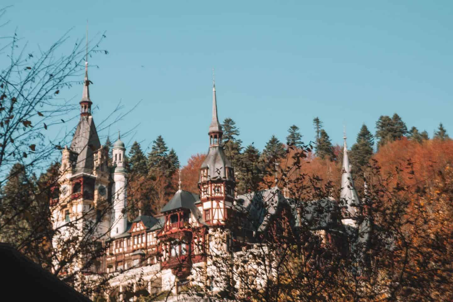 incredible view of peles castle with green and orange trees in the background