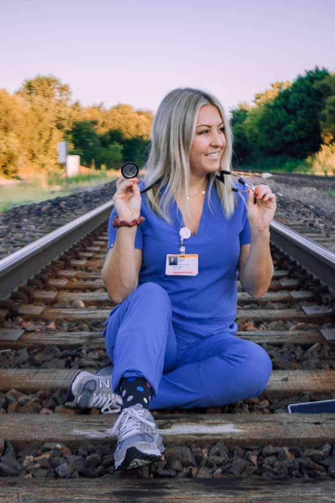 nurse in scrubs on railroad track