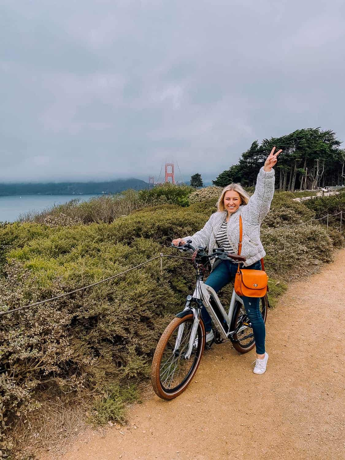 girl on biking with golden gate bridge in the background