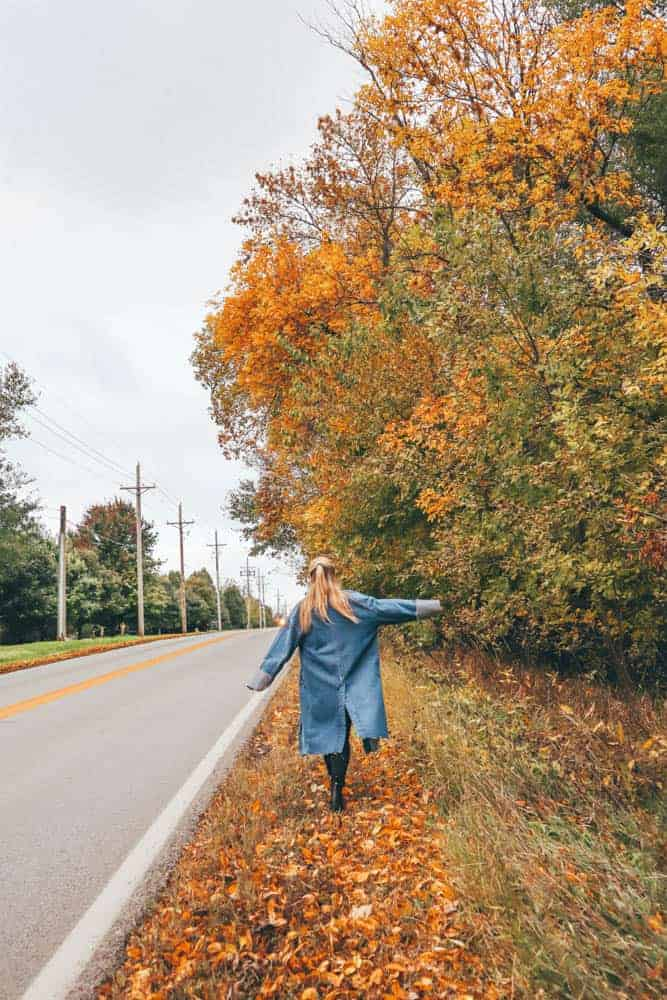 girl in denim jacket walking along bright orange and yellow leaves