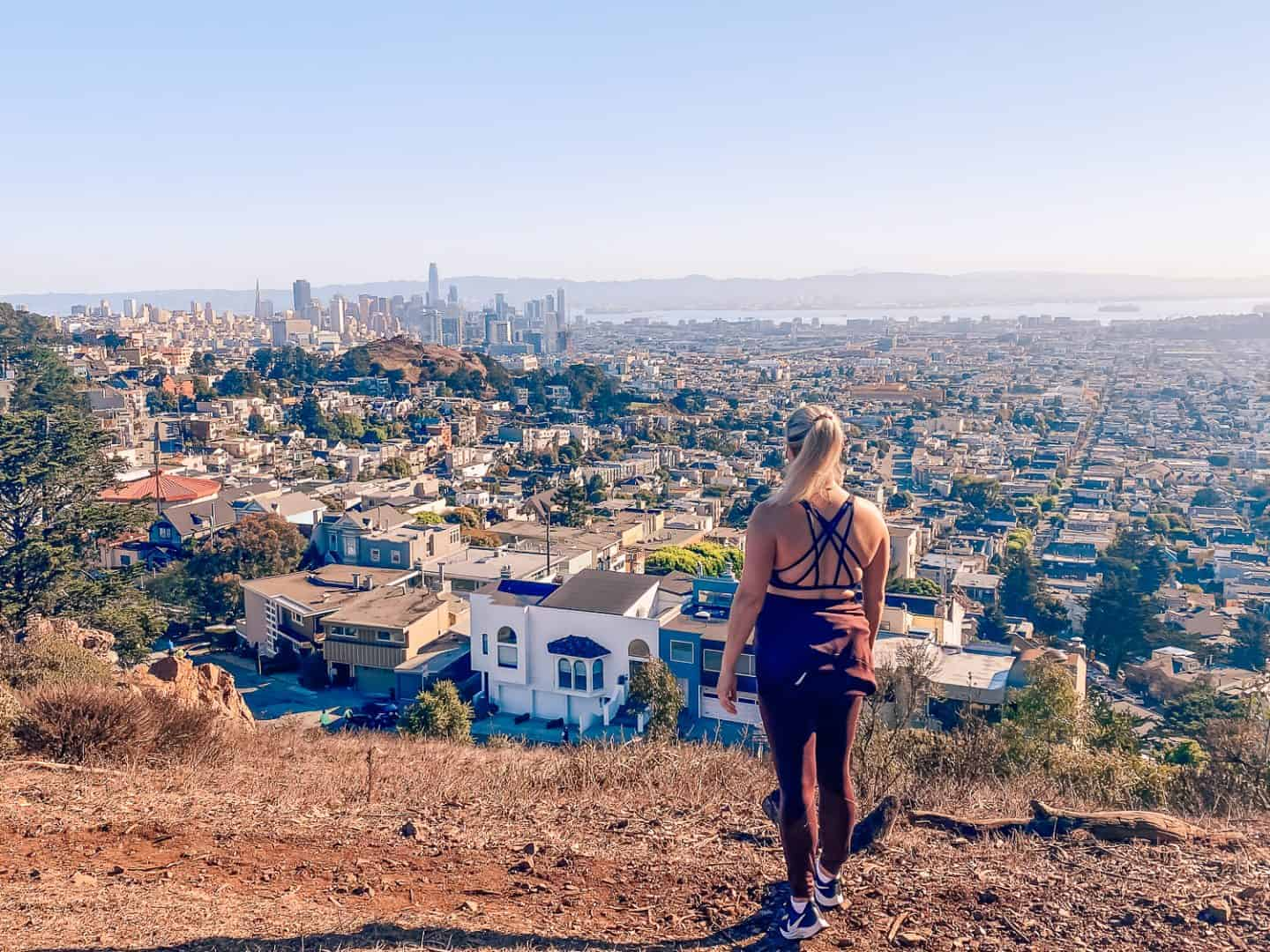 views of the SF skyline from tank hill with a girl in burgendy standing in front