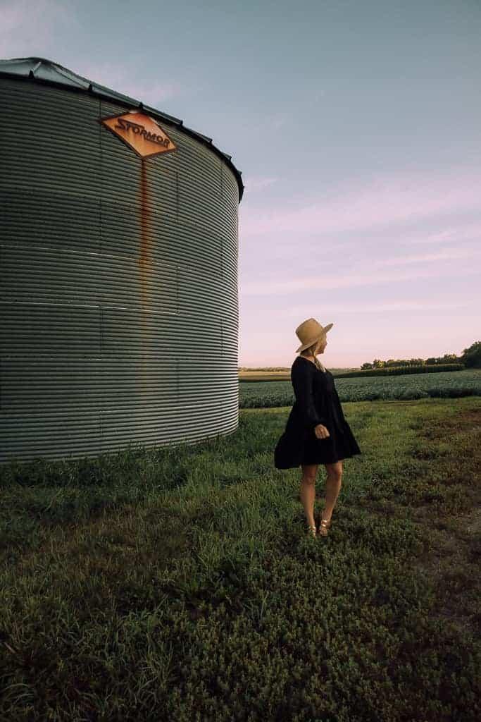 girl in black dress twirling around in big open field