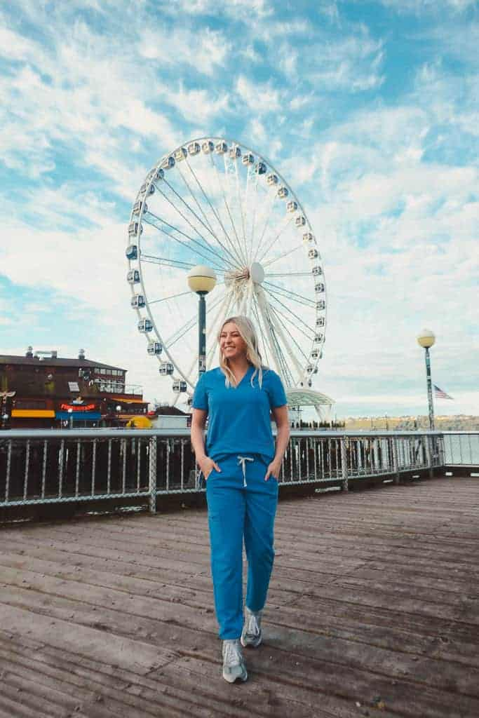 girl walking in front of ferris wheel