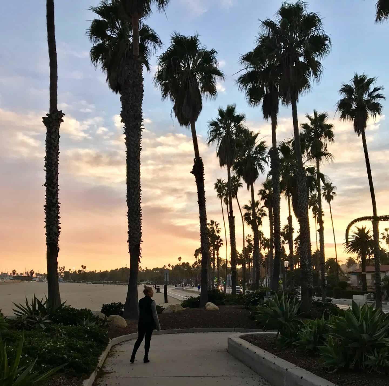 girl walking amongst big palm trees