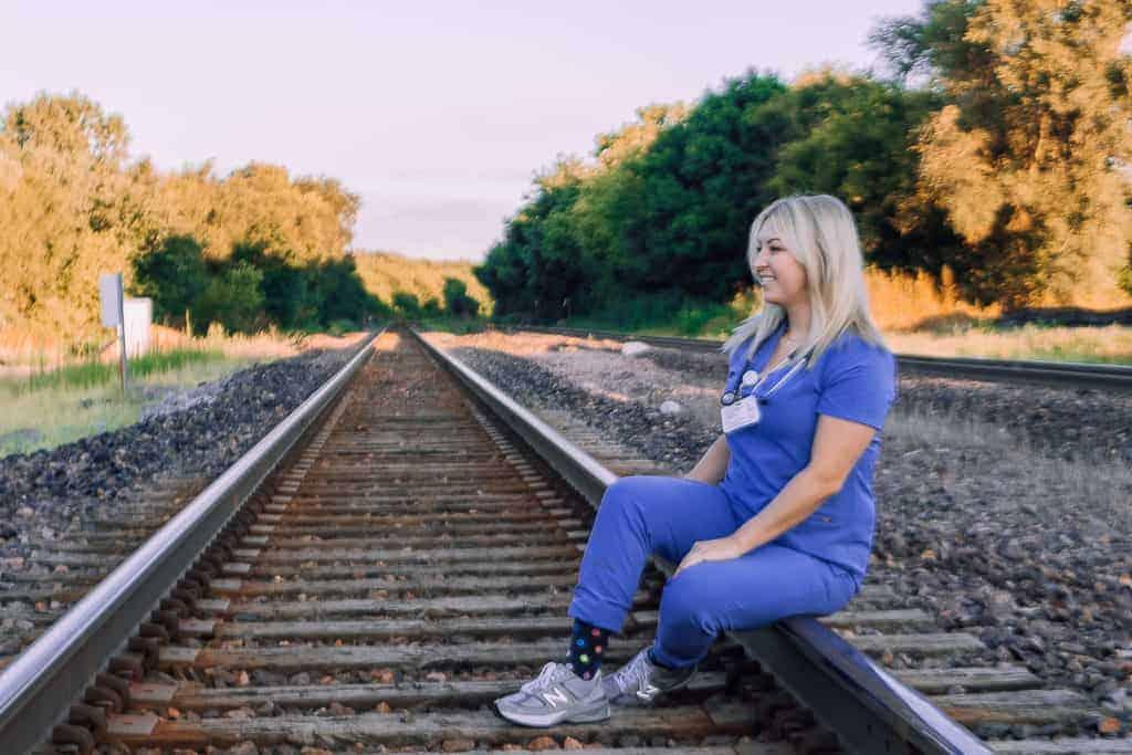 girl in scrubs on train tracks