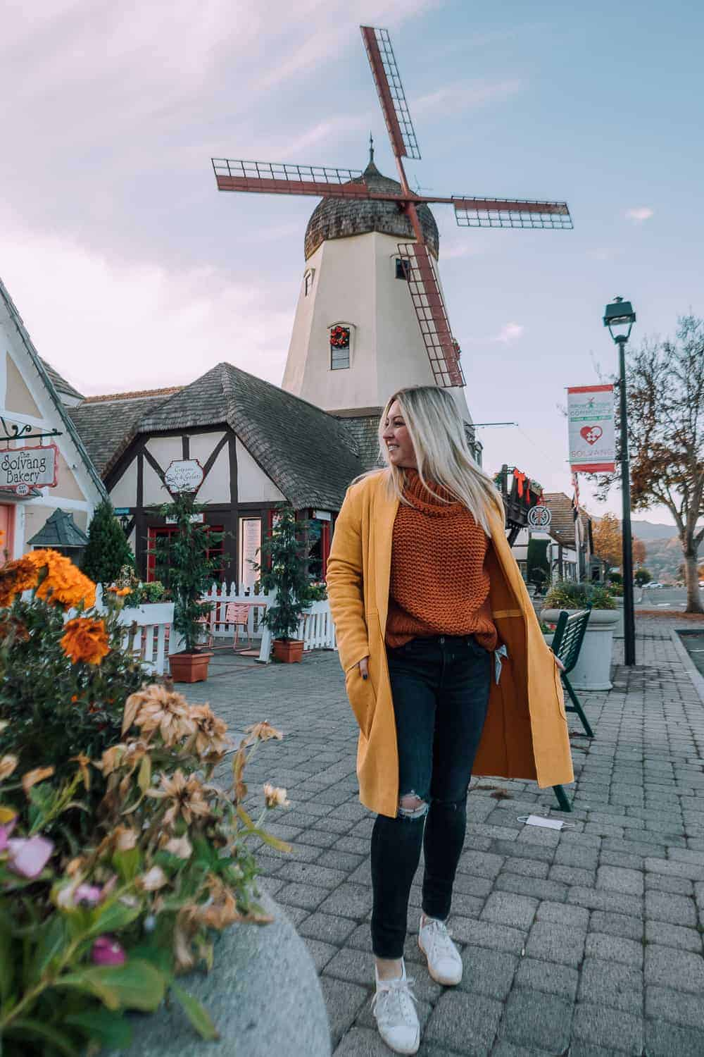 girl in orange sweater and yellow jacket in front of dutch windmill