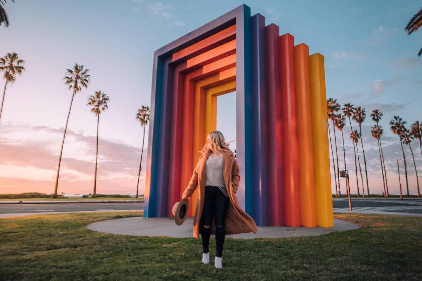 girls standing in front of rainbow colored structure as the sunrises creating a pink sky
