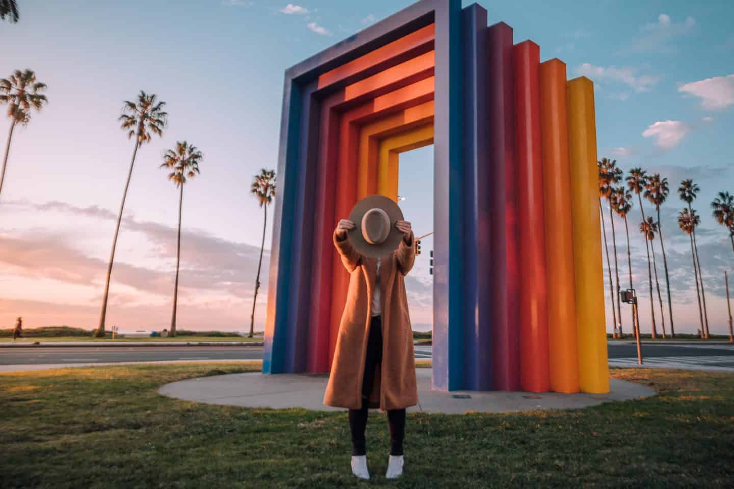 girl standing in front of rainbow gate with hat in front of her face