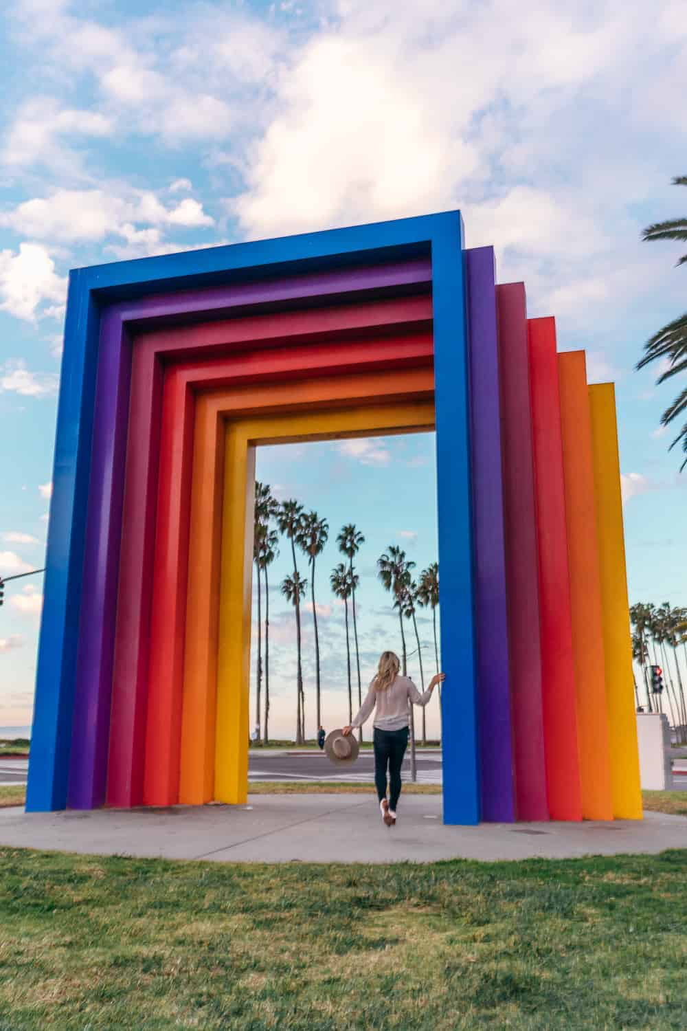 picture of girl under rainbow colored structure