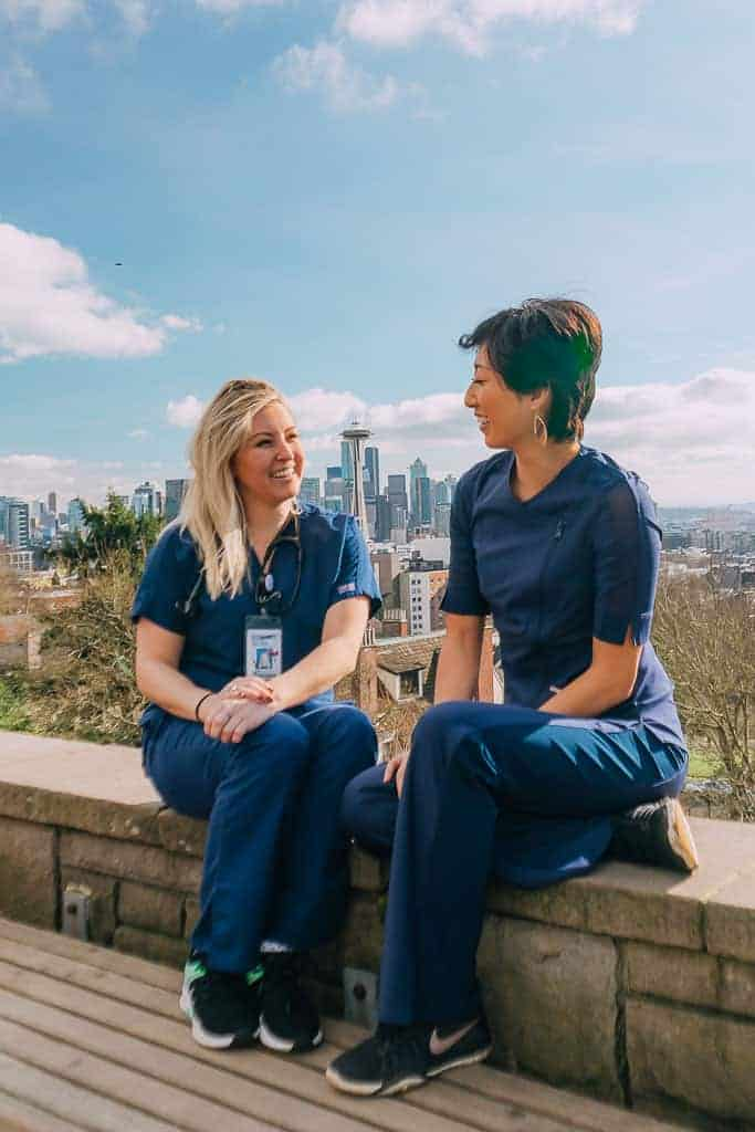 two nurses in blue scrubs in front of seattle skyline