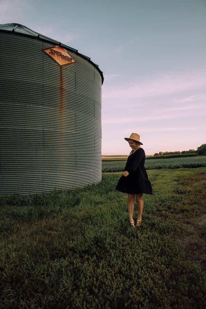 girl twirling around in open cornfield
