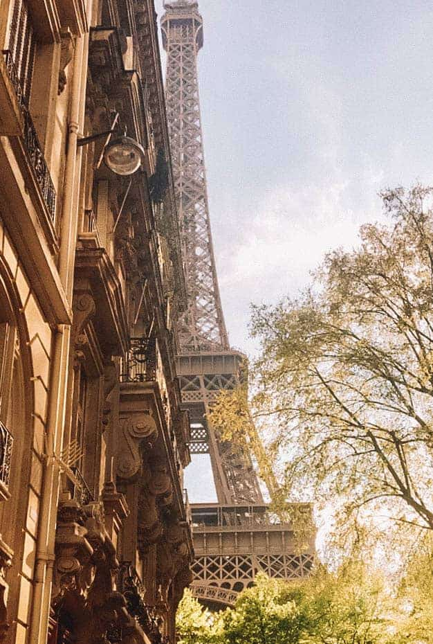 the beautiful eiffel tower peaking up behind a building