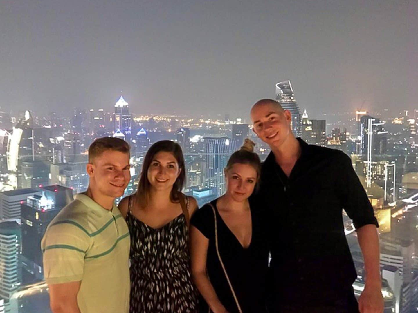 4 friends on a rooftop with the city in the background