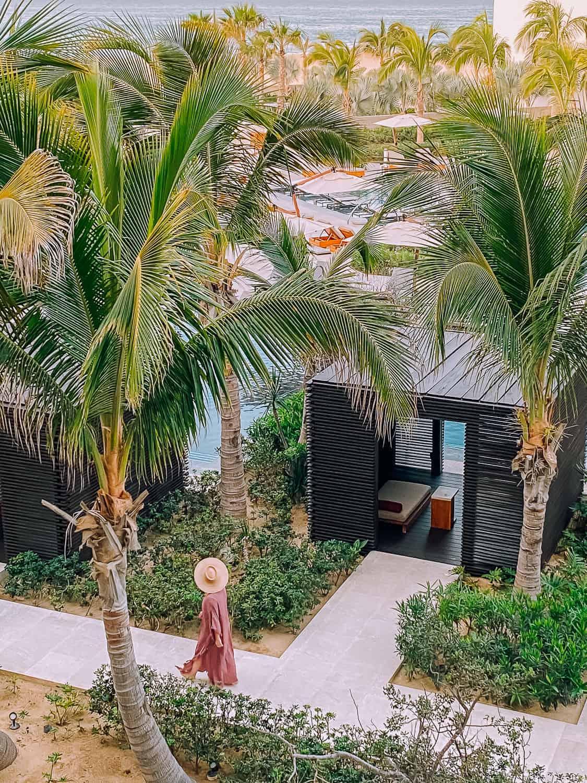 girl walking in purple dress amongst giant palm trees