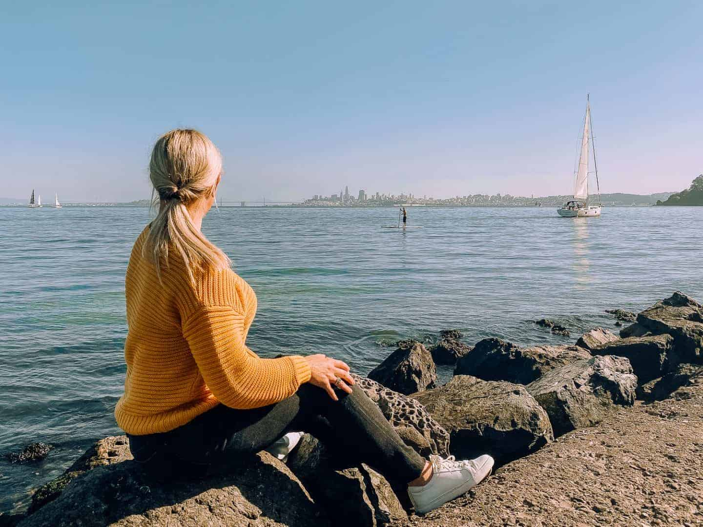 girl in yellow sweater staring out at san fran skyline across the bay