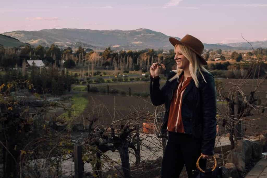 girl at winery in sonoma with rolling green hills