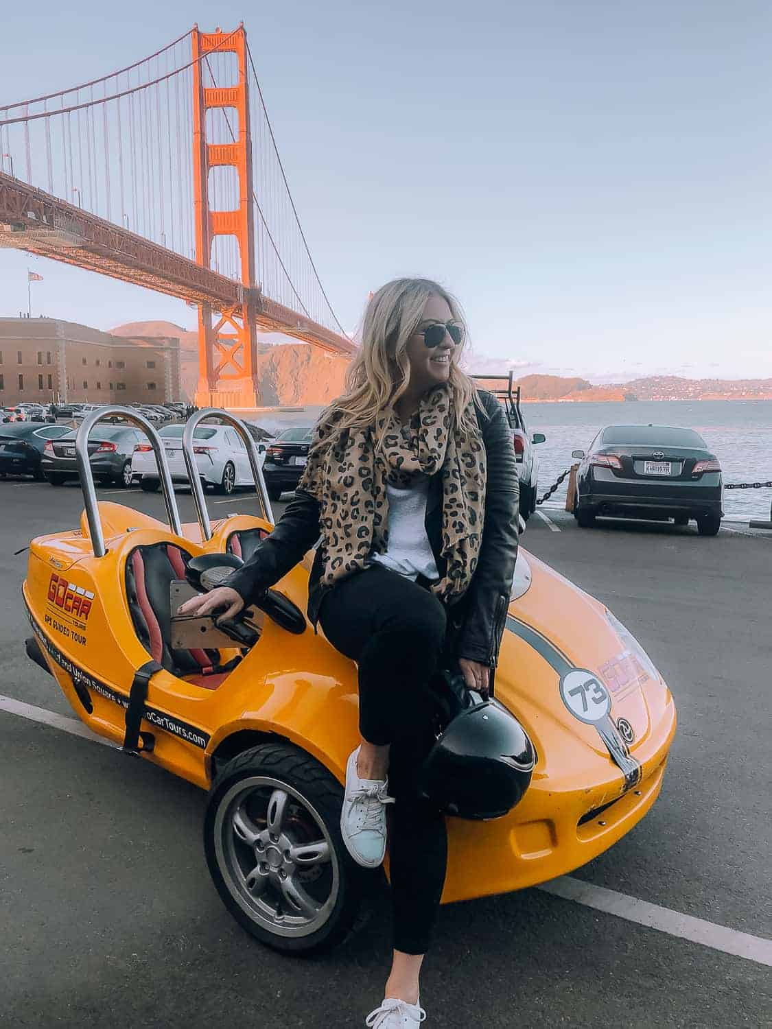 girl with yellow car in front of the golden gate bridge