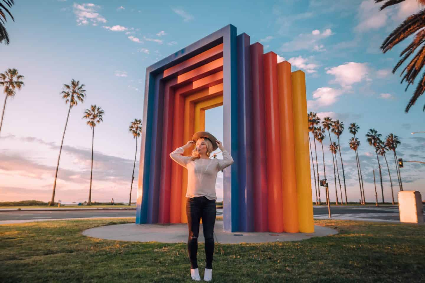 girl standing in front of rainbow structure in santa barbara