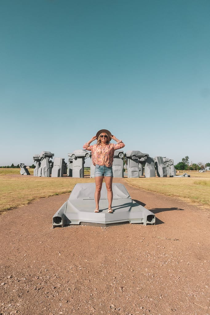 girl standing on old car buried in the ground