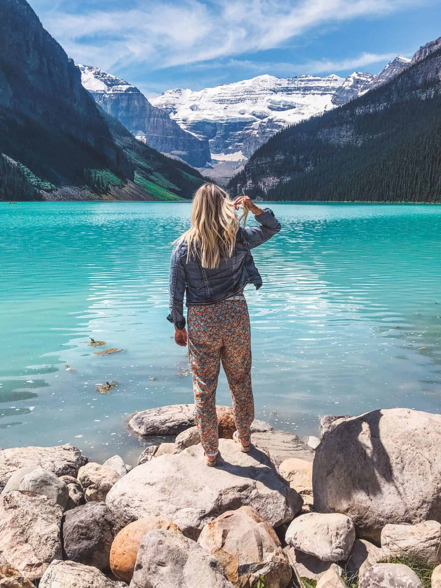 girl standing in front of icy blue lake