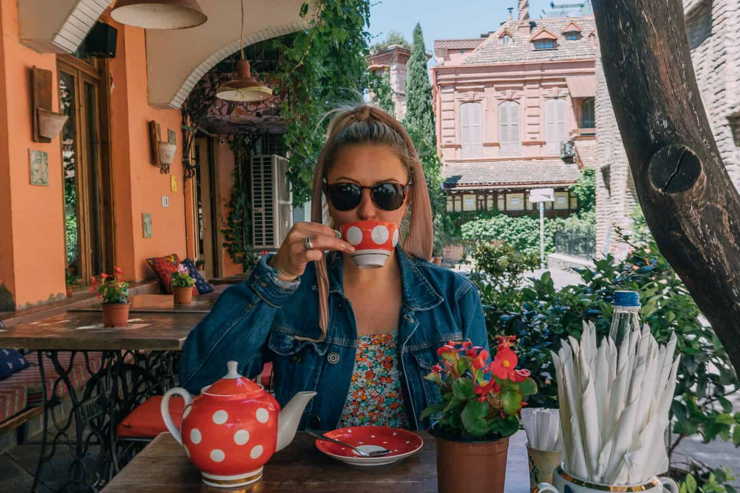 girl sipping tea out of red polka dot tea cup