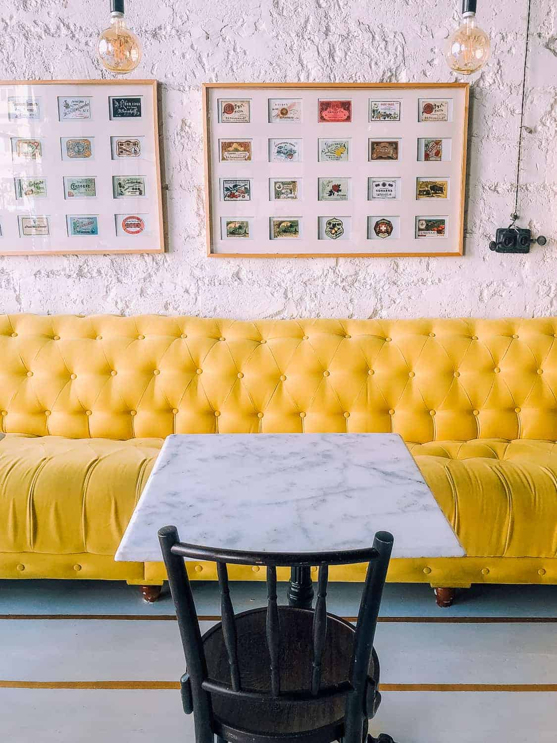 pretty cafe with a long yellow, plush bench