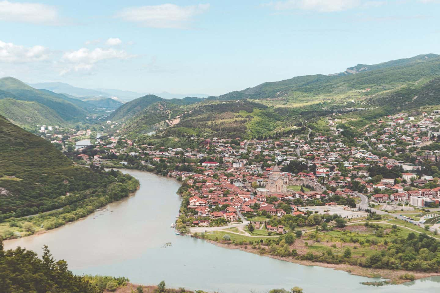 aerial views of the country with a river and small town in the distance