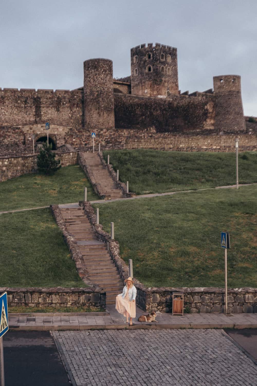 girl dancing in pink dress in front of castle
