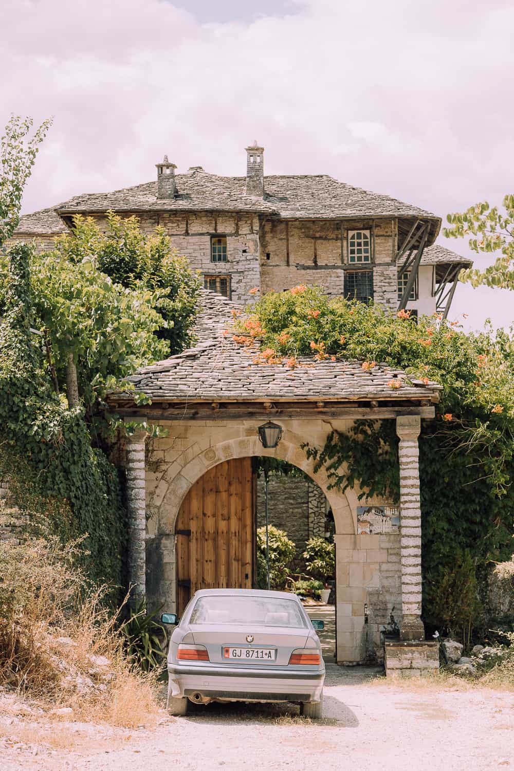 old house in albania with car parked out front